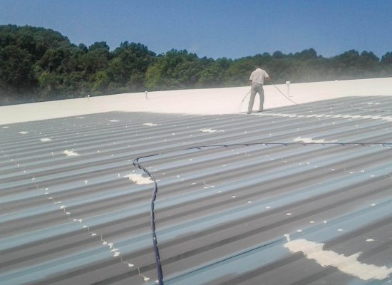 Worker applying the top coating on the Conklin liquid membrane roofing