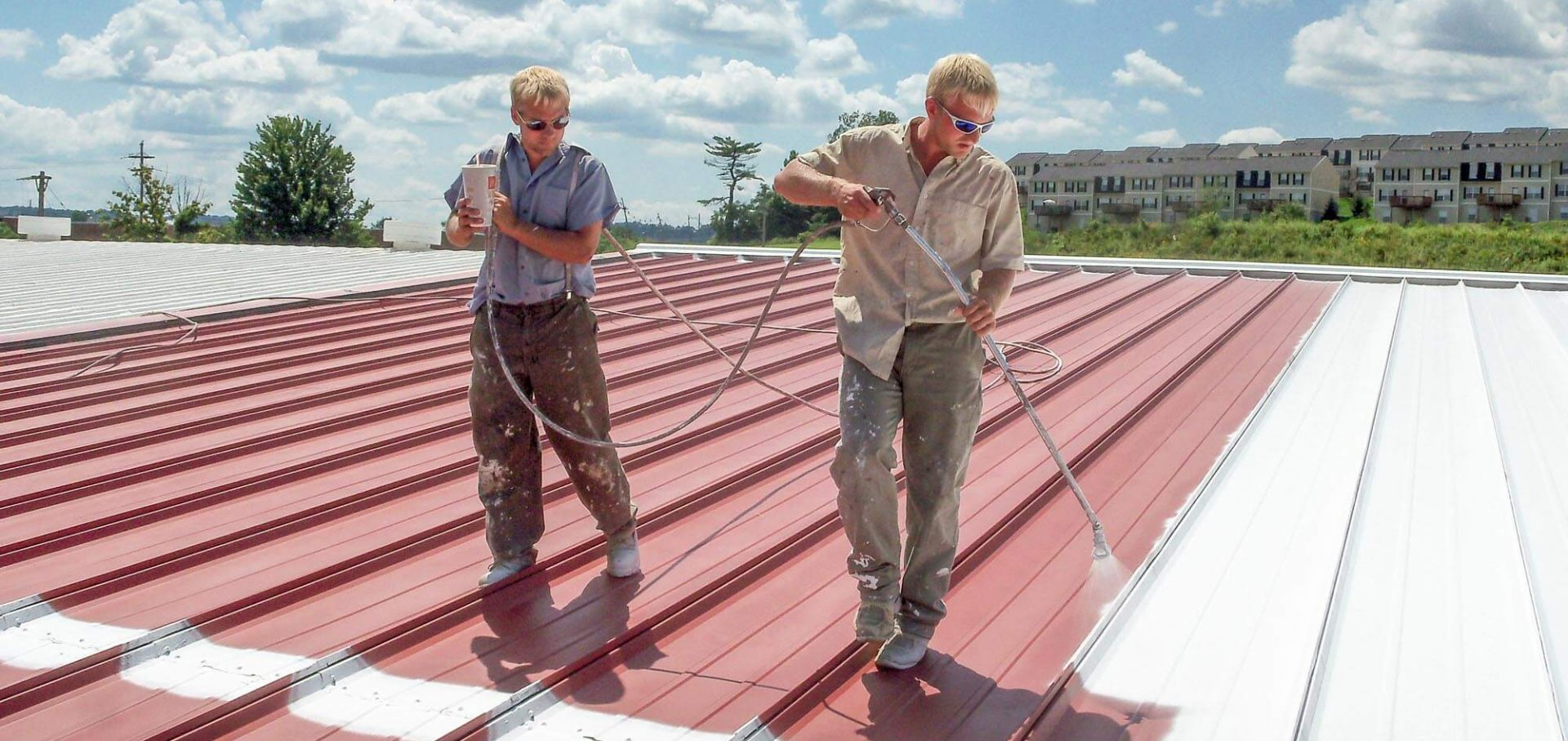 Two men applying Conklin liquid membrane roof coating