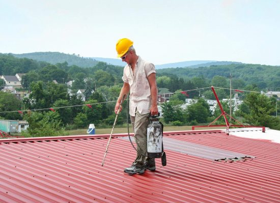worker sealing fasteners on metal roof